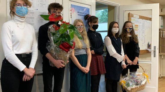 Rada Młodziżowa z kwiatami i prezentem na Dzień Nauczyciela