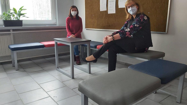 Pani dyrektor i pani Krzyżanowska prezentują nowe sidziska na korytarzu szkoły