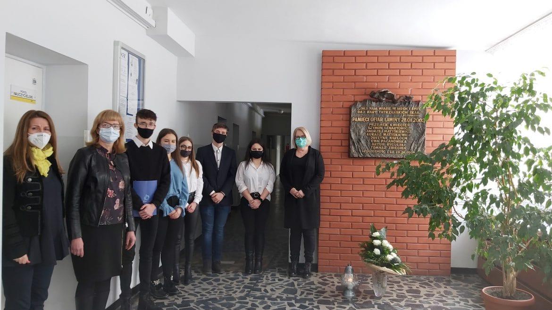 Zdjęcie z młodzieżą pod tablicą pamiątkową w szkole 28.01.2021